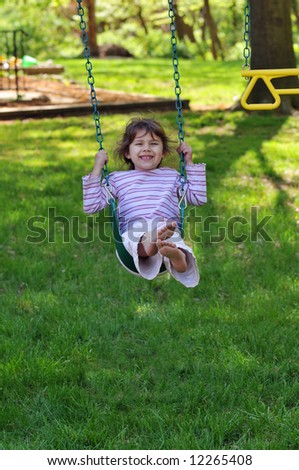 Little girls smiling and smiling on a swing