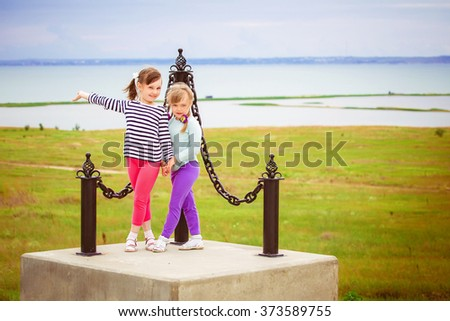 little girls standing on the background of the future bridge between Crimea and Russia - stock photo