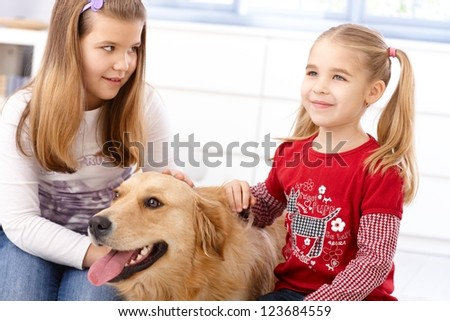 Little girls stroking dog at home, smiling.