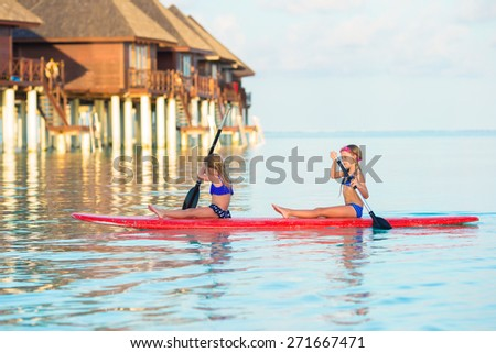 Little girls swimming on surfboard during summer vacation - stock photo