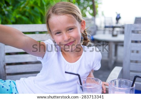 Little girls taking selfie and drinking tasty cocktails at outdoor cafe - stock photo