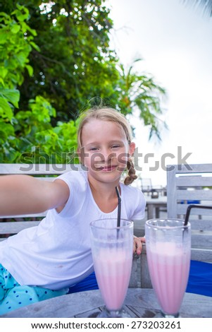 Little girls taking selfie and drinking tasty cocktails at tropical resort - stock photo