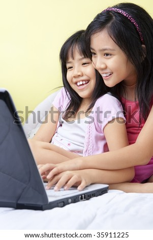 Little girls using laptop in their bedroom - stock photo