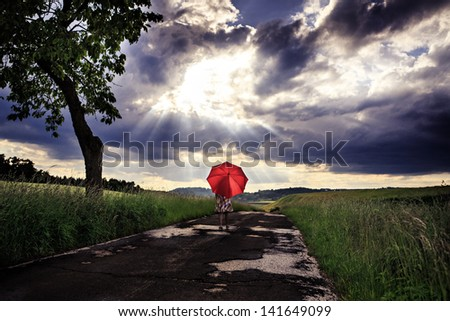 little girls walking on a road with an umbrella - stock photo