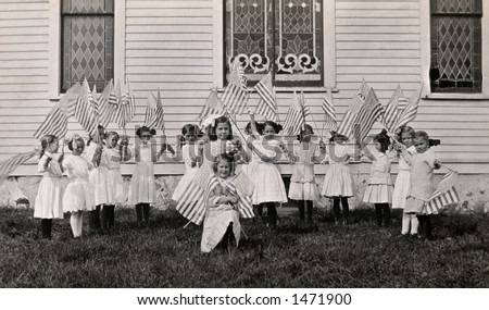 Little girls waving their American Flags in front of a church (stained glass windows) -  a circa 1915 vintage photograph - stock photo