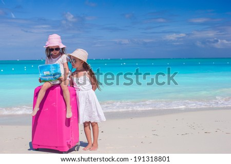 Little girls with big suitcase and a map searching the way on tropical beach - stock photo