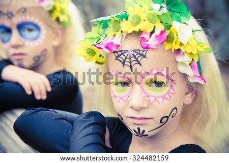 Little girls with black clothing and sugar skull makeup looking seriously at camera - stock photo