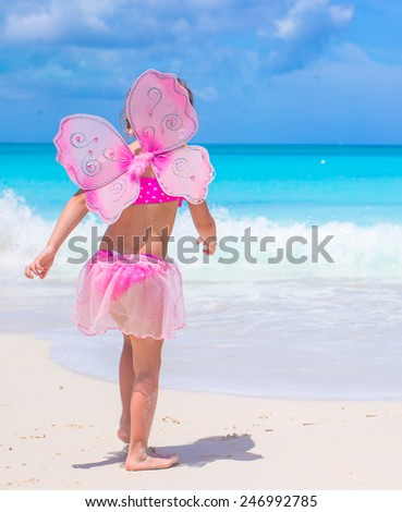 Little girls with butterfly wings have fun beach summer vacation - stock photo
