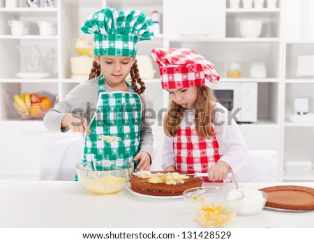 Little girls with chef hats preparing a cake in the kitchen - stock photo