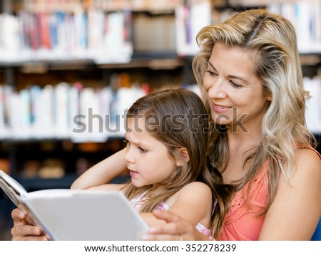 Little girls with their mother reading books in library - stock photo