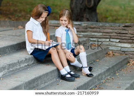 Little girls writting in exercise book in the park - stock photo