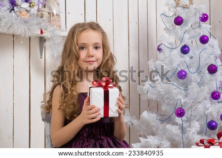 Little gLittle girl with christmas present in front of fir tree - stock photo