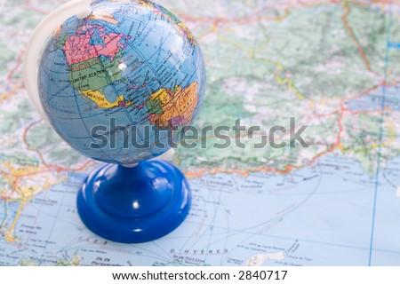 Little globe on a map. - stock photo