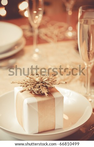 Little gold ribboned gift with gold background - stock photo