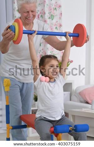 little granddaughter doing exercise - stock photo