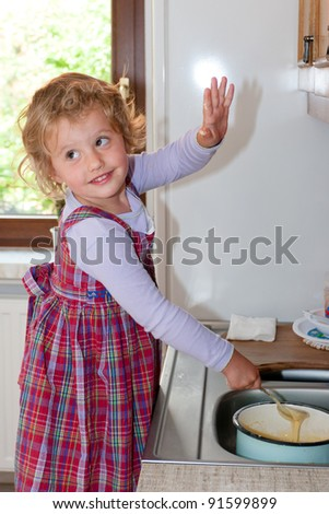 Little granddaughter helping grandma in a kitchen - stock photo