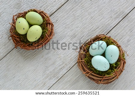 Little green and blue speckled easter eggs in mossy vine nests on rustic wooden background - stock photo