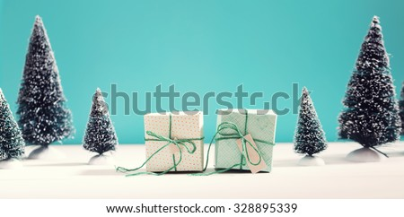 Little green handmade gift boxes in a snow covered miniature evergreen forest - stock photo