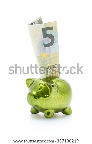 Little green piggy bank with five euro banknote inserted - stock photo