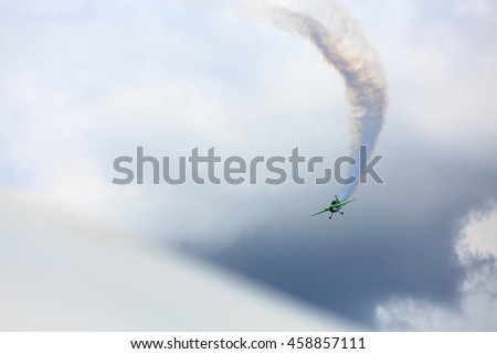 Little green plane performs aerobatics in the sky. - stock photo