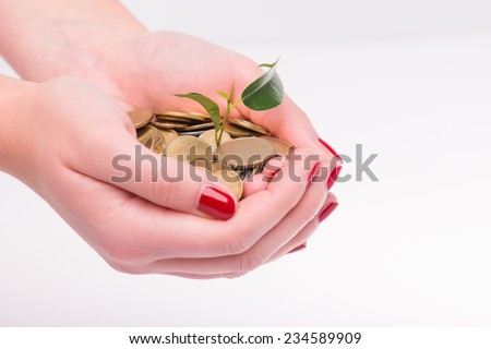 Little green plant growing in a heap of coins lying in the hands of woman isolated on white background. Concept of new life - stock photo