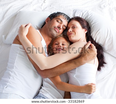 Little gril relaxing on bed with her parents at home