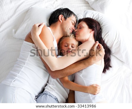 Little gril sleeping on bed with her parents at home - stock photo