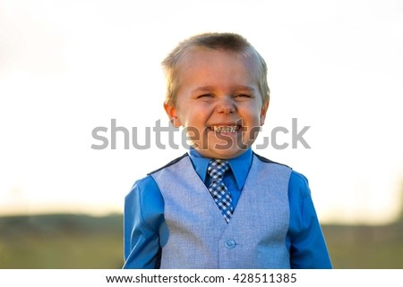 Little guy in his suit making a big smile against the summer sun - stock photo