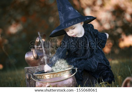 Little halloween witch , boiling a potion, outdoors in the woods