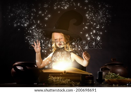 Little Halloween witch reading conjure from magic book - stock photo