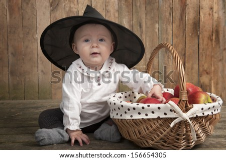little halloween witch with basket full of apples - stock photo