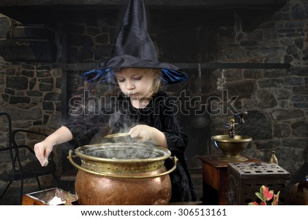 little halloween witch with cauldron