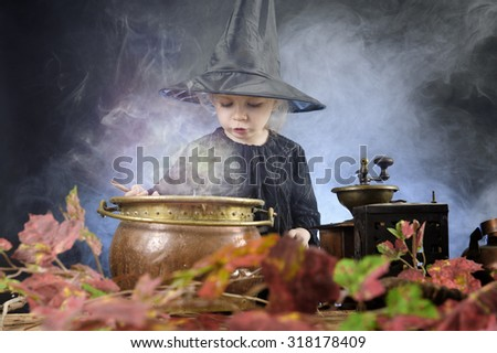 little halloween witch with cauldron and smoke - stock photo