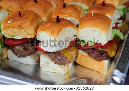 Little hamburgers with lettuce, tomato and cheese ready to serve - stock photo