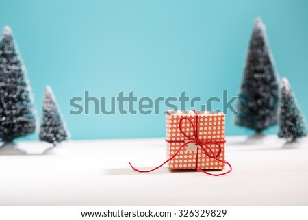 Little handmade gift box in a snow covered miniature evergreen forest - stock photo