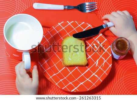 Little hands eating a bread and drinking milk. - stock photo