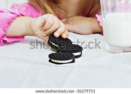 Little hands reaching for a creme filled cookies. - stock photo