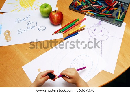 Little hands sharpening a pencil between school supplies and apples. - stock photo