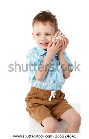 Little handsome boy listens to the sea through the shell - stock photo