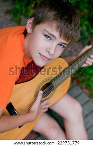 little handsome boy playing guitar, outside, smiling in the camera - stock photo