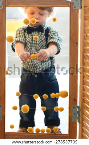 Little handsome son stands behind screen with yellow balls. Focus on balls - stock photo