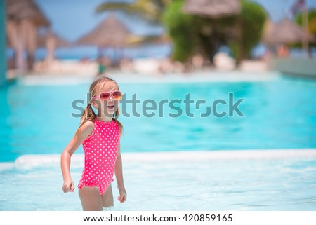 Little happy adorable girl in outdoor swimming pool - stock photo