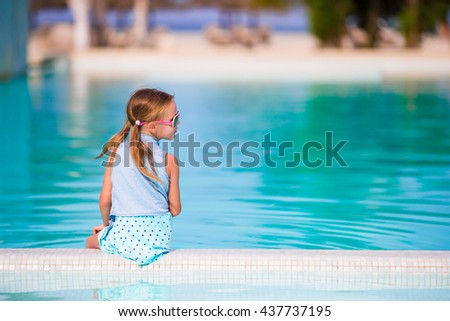 Little happy adorable girl in outdoor swimming pool. Beautiful teenager girl enjoy vacation at tropical exotic hotel outdoors. - stock photo