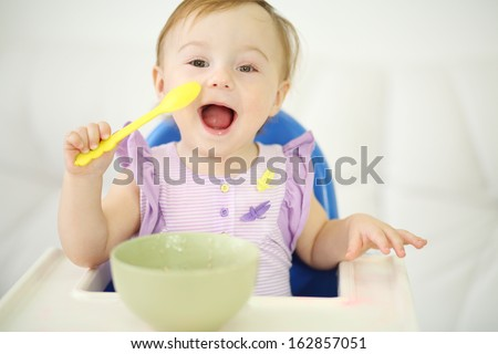 Little happy baby with spoon sits at highchair and eats porridge on plate. Shallow depth of field. - stock photo