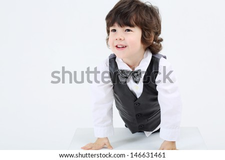 Little happy boy based on large cube and looks aside on white background.