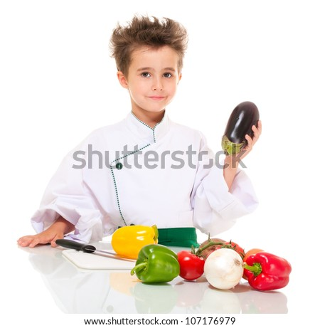 Little happy boy chef in uniform with knife cooking vegetables holding aubergine isolated on white - stock photo