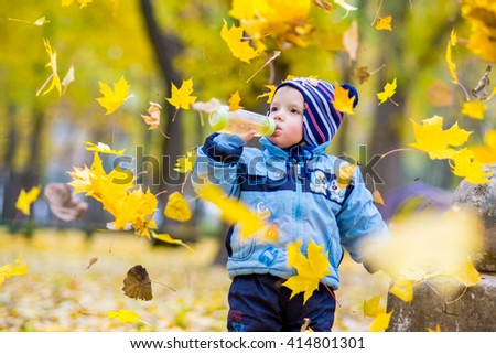 Little happy boy in blue jacket is playing with leaves at golden autumn park background. - stock photo