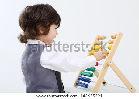Little happy boy in vest plays with colorful abacus in white studio. - stock photo