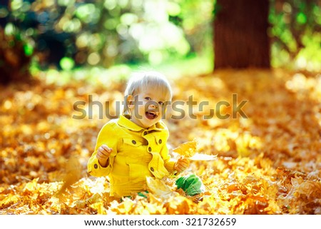 Little happy boy in yellow jacket is playing with leaves at golden autumn park background.