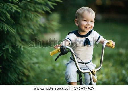 little happy boy on bike portrait - stock photo